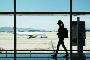Silhouette of Young Woman Walking at Airport by Nomad Soul