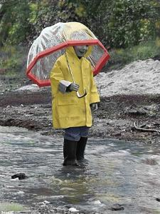 Child in Rain Gear with Umbrella Playing in Puddle. by Nora Hernandez