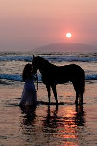 Girl with a Horse in the Water at Sunset by Nora Hernandez