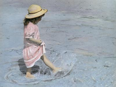 Little Girl Playing in Water on Beach