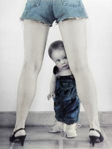 Toddler Standing Behind Woman's Legs Looking Through by Nora Hernandez