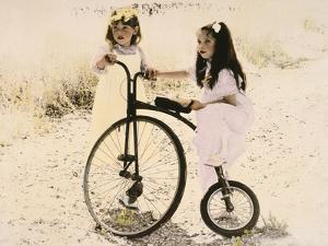 Two Little Girls by an Old Fashioned Bicycle by Nora Hernandez