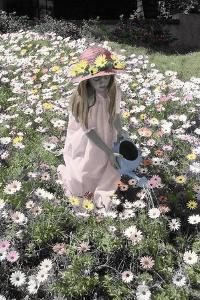 Young Girl in a Field of Flowers Watering Them by Nora Hernandez