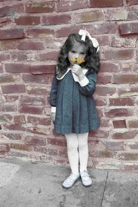 Young Girl Standing in Front of a Stone Wall Smelling a Flower. by Nora Hernandez