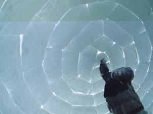 A Man Places the Last Block in an Igloo He is Constructing by Norbert Rosing