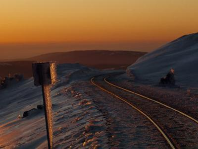 Railroad Tracks at Sunset in an Icy Mountain Landscape
