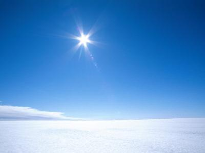 The Sun Appears as a Bright Pointed Star in a Crisp Blue Polar Sky by Norbert Rosing