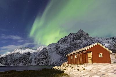 Northern Lights (Aurora Borealis) Illuminate Snowy Peaks and Wooden Cabin on a Starry Night-Roberto Moiola-Photographic Print