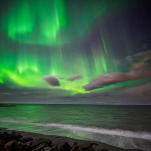 Northern Lights over the Waves Breakiing on the Beach in Seltjarnarnes, Reykjavik, Iceland