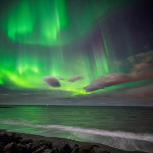 Northern Lights over the Waves Breakiing on the Beach in Seltjarnarnes, Reykjavik, Iceland