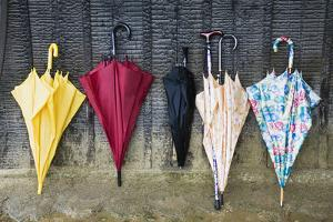 Colorful Umbrellas Leaning against a Wall by Nosnibor137