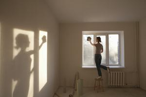 Full Length Rear View of Young Woman Cleaning Window in New Apartment by Nosnibor137