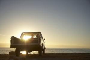 Rear View of Young Couple in Pick-Up Truck Parked in Front of Ocean Enjoying Sunset by Nosnibor137
