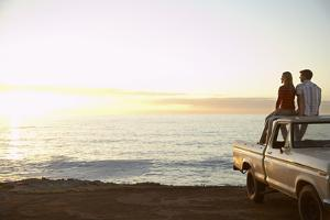 Rear View of Young Couple on Pick-Up Truck Parked in Front of Ocean Enjoying Sunset by Nosnibor137