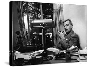 Novelist and Script Writer William Faulkner Smoking a Pipe at His Desk at Warner Brothers Studios