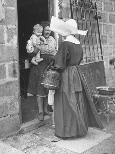 Nun from the Order of Sisters of Charity Visiting a Destitute Family with Supplies--Photographic Print