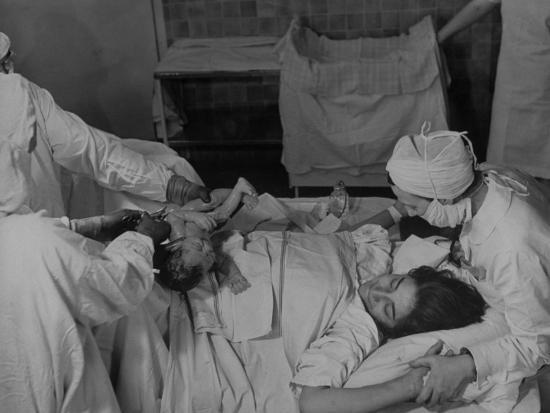 """Nurse at Her Head and Holding Her Hands, as She Gazes at Her Baby Boy after """"Painless"""" Childbirth-Alfred Eisenstaedt-Premium Photographic Print"""