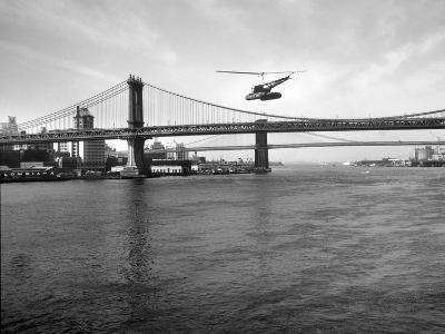 NYC Police Helicopter Hovering over the East River Next to the Manhattan Bridge--Photographic Print
