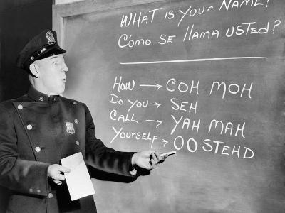NYC Police Officer Practices Basic Spanish Phrases Written on Blackboard, Ca. 1955--Photo