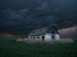 Old Barn Stands in a Wheat Field as a Thunderstorm Passes in the Distance Near Ogallah, Kansas