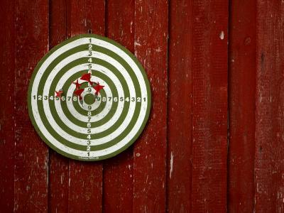 Old Dart Board Game Hanging on a Weathered Red Wall--Photographic Print
