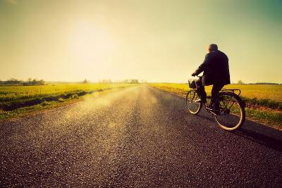 Old Man Riding A Bike On Asphalt Road Towards The Sunny Sunset Sky-Michal Bednarek-Art Print