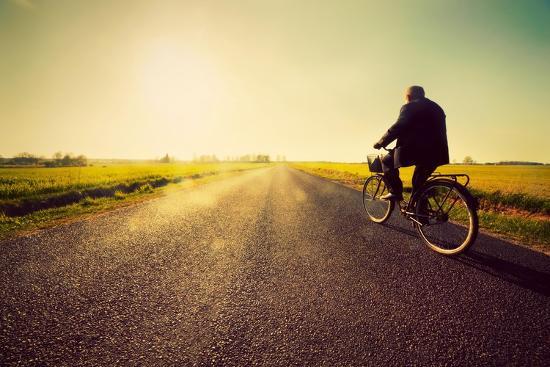 Old Man Riding A Bike On Asphalt Road Towards The Sunny Sunset Sky Art  Print by Michal Bednarek | Art com