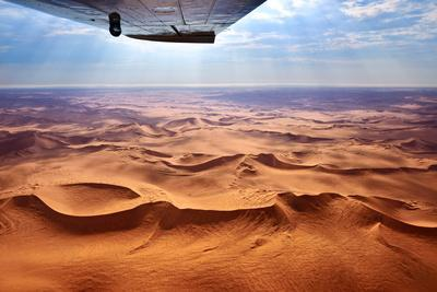 Beautiful Landscape of the Namib Desert under the Wing of the Aircraft at Sunset. Flying on a Plane