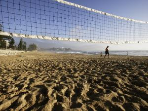 Person Jogging Near Volleyball Net on Manly Beach, Early Morning by Oliver Strewe