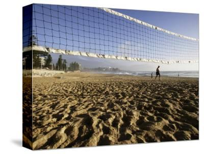 Person Jogging Near Volleyball Net on Manly Beach, Early Morning