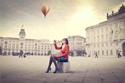 Beautiful Woman In Colored Clothes On A Square With Hot-Air Balloon In The Background by olly2