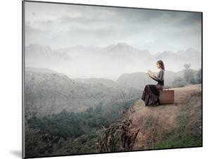 Woman Sitting On A Suitcase And Reading A Book With Landscape On The Background by olly2
