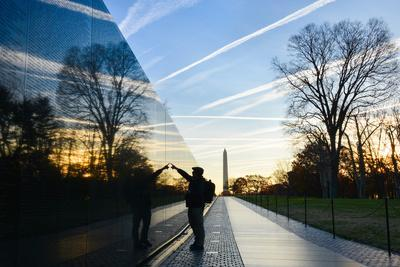 Washington DC - A Veteran Looks for a Name at Vietnam Veterans Memorial Wall at Sunrise