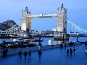 People Walking Along Queens Walk on the Thames at Dusk with Tower Bridge in the Background by Orien Harvey
