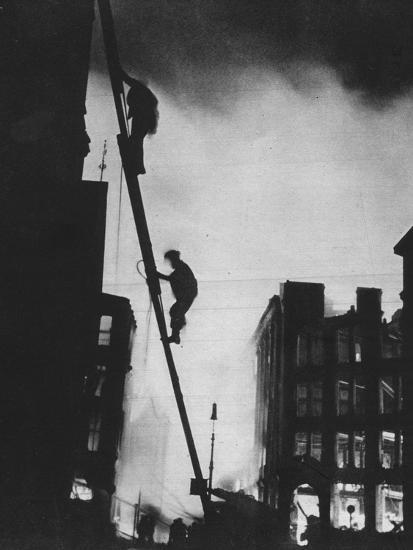 'Out in the Blitz, silhouetted aganinst the light of fires, rescue men climb into a building in St-Unknown-Photographic Print