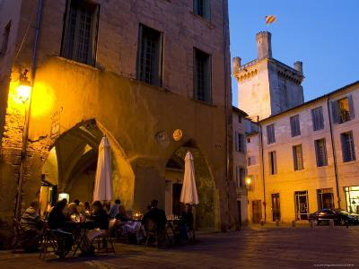 Outdoor Dining in Uzes, with Duche D'Uzes Illuminated at Dusk-Glenn Beanland-Photographic Print