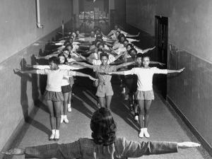 Overcrowded Students Enduring Calisthenics in an Unused Hallway in their All Black High School