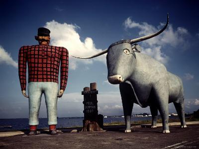Painted Concrete Sculpture of Paul Bunyon and His Blue Ox, Babe Standing on Shores of Lake Bemidji-Andreas Feininger-Photographic Print