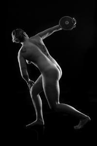 Naked tattooed female discus thrower against black background by Panoramic Images