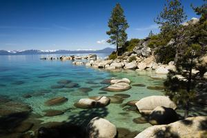Rocks in a lake with mountain range in the background, Lake Tahoe, California, USA by Panoramic Images