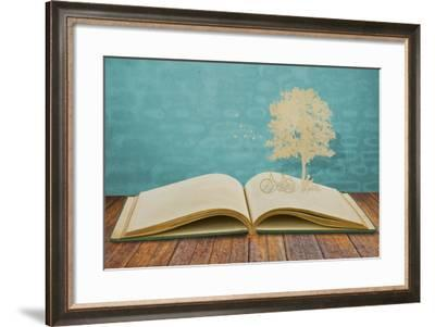 Paper Cut Of Children Read A Book Under Tree On Old Book-jannoon028-Framed Art Print