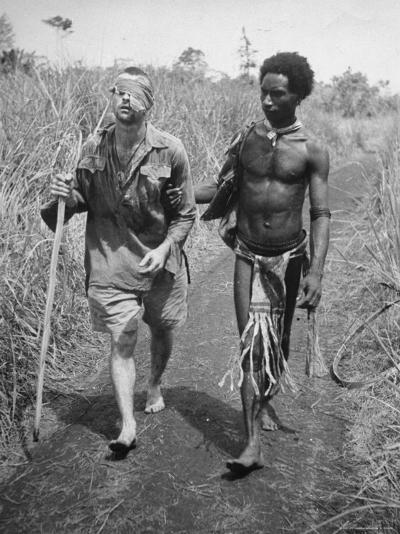 Papuan Native Helping a Wounded Australian Infantryman Along Road Away from the Buna Battlefront-George Silk-Photographic Print