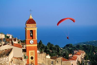 Paraglider Soaring past Tower of Colourful Village Church, Alpes-Maritimes, Roquebrune, Provence-Al-David Tomlinson-Photographic Print