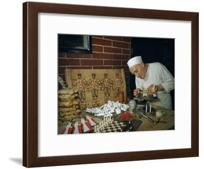 Pastry Chef Decorates a Cake Near Other Edible Sculptural Creations-Volkmar K^ Wentzel-Framed Photographic Print