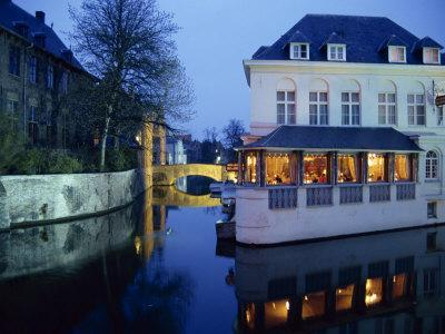 Reflections in the Canals of Restaurant and Bridge, Illuminated in the Evening, in Bruges, Belgium