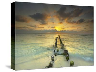 Sunset Behind an Old Eroded Pier Extending into the Ocean Near Cancun, Mexico