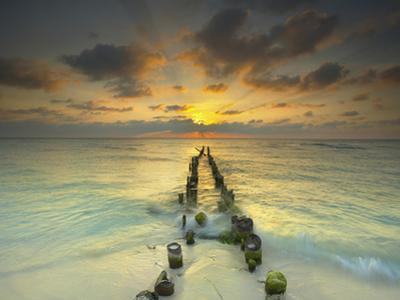 Sunset Behind an Old Eroded Pier Extending into the Ocean Near Cancun, Mexico by Patrick Smith