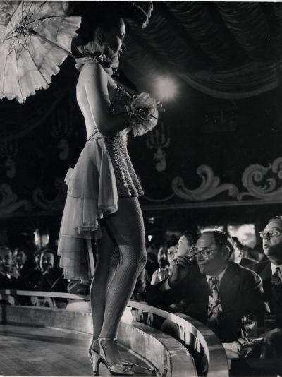 Patron at Stage-Side Table Looks Appraisingly at Tall Show Girl Standing at Edge of Stage-Gjon Mili-Photographic Print