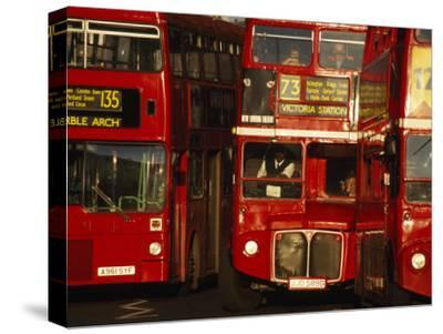 Travelers on Traditional Red Buses in London