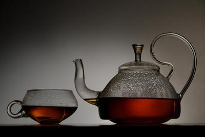 A Clear Glass Tea Pot Full of Hot Tea Sits Next to a Clear Glass Tea Cup with Tea